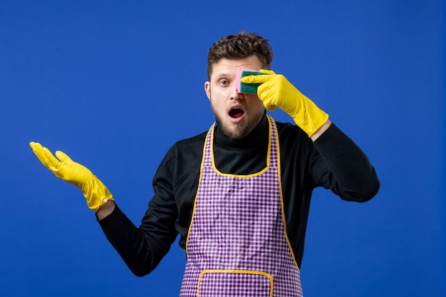 Front view of wondered male housekeeper holding up sponge in front of his eye on blue wall