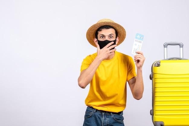 전면보기는 여행 티켓을 들고 노란색 가방 근처에 서있는 노란색 티셔츠에 남성 관광객을 궁금해