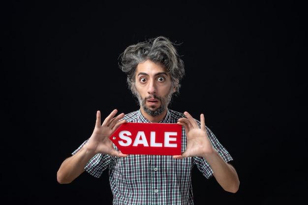 Vista frontale dell'uomo meravigliato che tiene il segno di vendita sul muro scuro