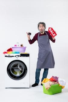 Вид спереди удивленный человек, держащий открытку и знак продажи, стоящий возле корзины для белья стиральной машины на белой стене