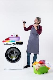 正面図は白い壁の洗濯機の洗濯かごの近くに立っているカードを持っている男を不思議に思った