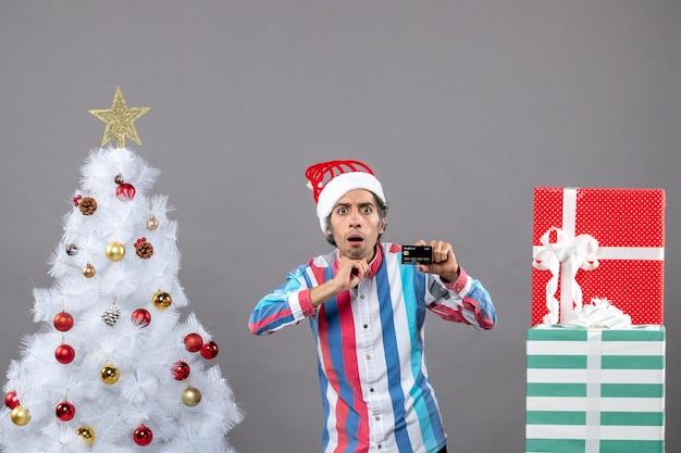 크리스마스 트리 근처 서 그의 턱에 손을 넣어 전면보기 궁금 남자