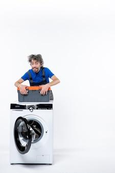 Vista frontale del riparatore meravigliato in piedi dietro la lavatrice che mette la borsa degli attrezzi sulla macchina sul muro bianco
