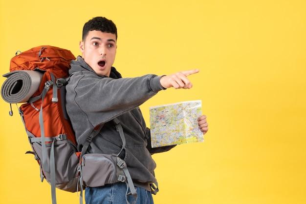 Вид спереди удивился путешественник с рюкзаком, держащим карту
