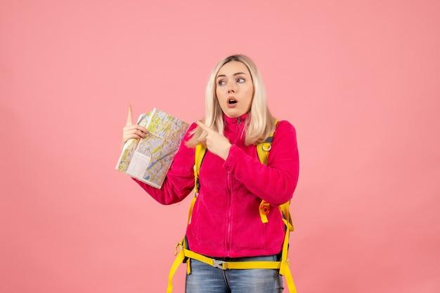 Вид спереди удивленная женщина-путешественница с желтым рюкзаком, держащая карту