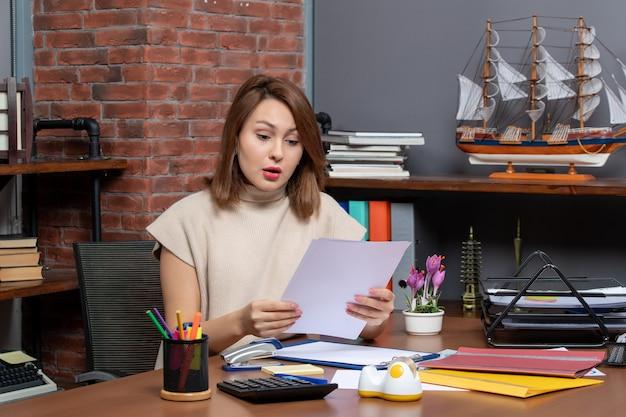 Vista frontale della donna meravigliata che controlla i documenti seduta in ufficio