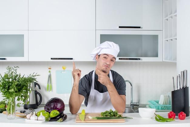 La vista frontale si chiedeva un giovane cuoco in uniforme che indicava l'armadio nella cucina moderna
