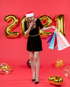 Front view wondered young lady in black dress holding shopping bags balloons on red