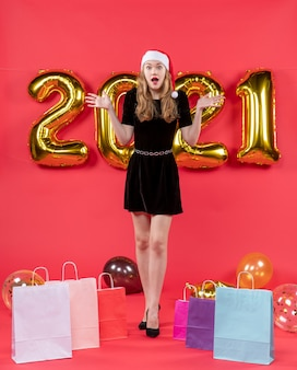 Front view wondered young lady in black dress shopping bags on floor balloons on red