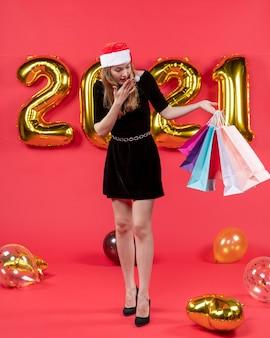 正面図は、赤のショッピング バッグの風船を保持している黒のドレスを着た若い女性を疑問に思った