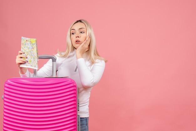 正面図は地図を見てピンクのスーツケースの後ろに立っている若い女性を不思議に思った