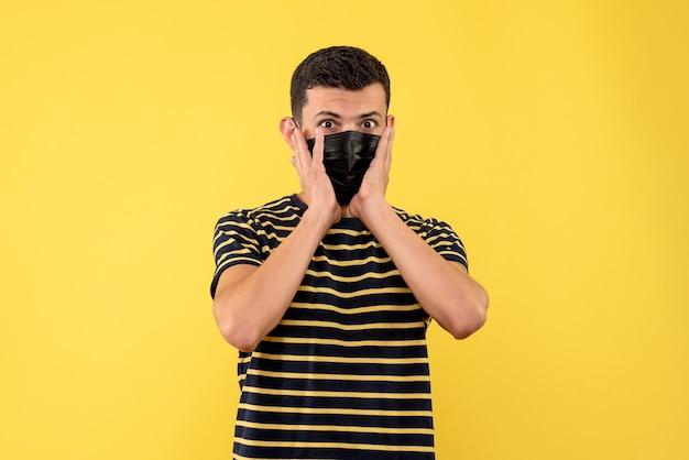 전면보기는 흑백 줄무늬 티셔츠 노란색 배경에서 젊은 남자를 궁금해
