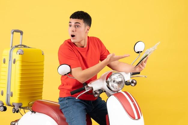 Вид спереди удивился молодой человек в красной футболке на мопеде, держащем карту