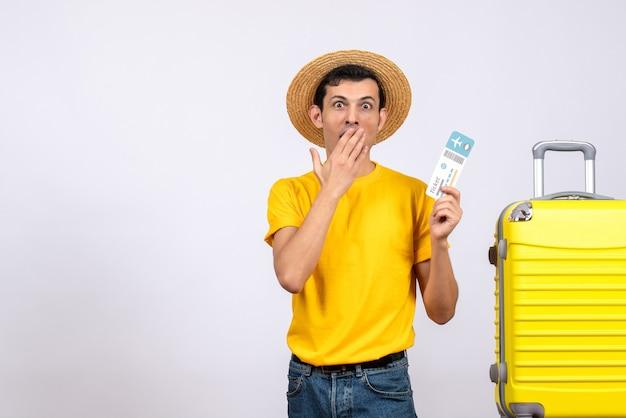 전면보기는 티켓을 들고 노란색 가방 근처에 서있는 노란색 티셔츠에 젊은 남자를 궁금해