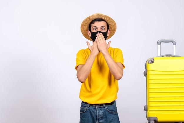 正面図は、顔に手を置いて旅行チケットを保持している黄色のスーツケースの近くに立っている黄色のtシャツを着た若い男を不思議に思った