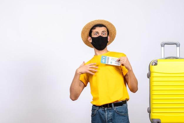 正面図は、旅行のチケットを保持している黄色のスーツケースの近くに立っている黄色のtシャツを着た若い男を不思議に思った