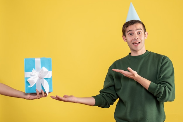 Front view wondered young man pointing at gift in human hand on yellow