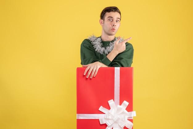전면보기는 노란색에 큰 giftbox 뒤에 서있는 젊은 남자를 궁금해