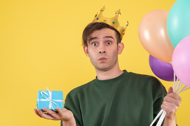 Вид спереди удивился молодой человек с короной, держащий воздушные шары на желтом