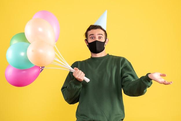 전면보기 파티 모자와 노란색에 서있는 다채로운 풍선 젊은 남자 궁금