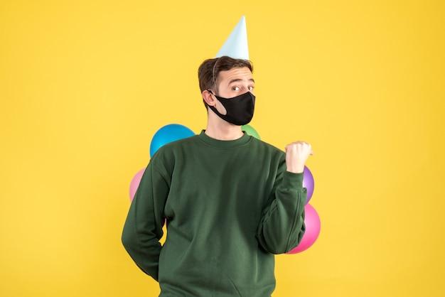 正面図は、黄色の上に立っているパーティーキャップとカラフルな風船を持つ若い男を疑問に思いました
