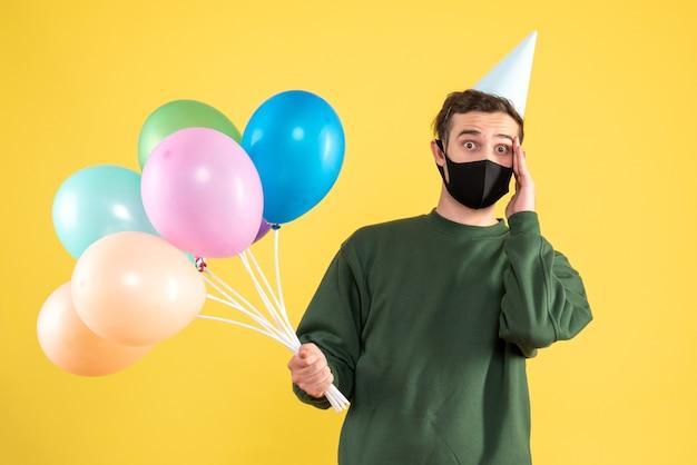 Vista frontale si chiedeva il giovane con cappello da festa e palloncini colorati in piedi sul giallo