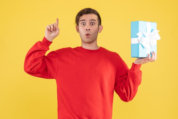 Вид спереди удивился молодой человек с красным свитером, указывая пальцем на потолок на желтом