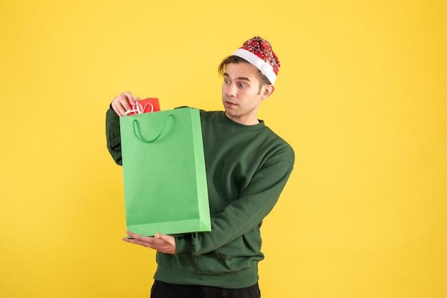 Вид спереди удивился молодой человек в шляпе санта-клауса, держащий зеленую сумку для покупок и подарок, стоящий на желтом