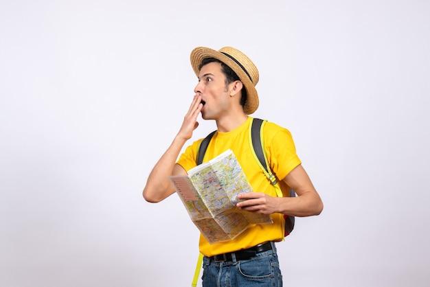 Вид спереди удивился молодой человек в соломенной шляпе и желтой футболке, держащий карту