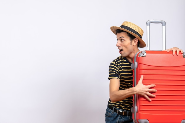 Вид спереди удивился молодой человек в соломенной шляпе, держащий чемодан