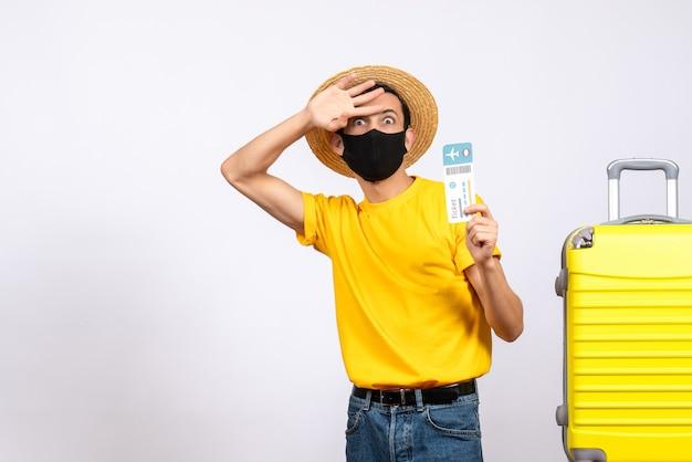 正面図は、旅行チケットを保持している黄色のスーツケースの近くに立っている麦わら帽子を持つ若い男を疑問に思いました
