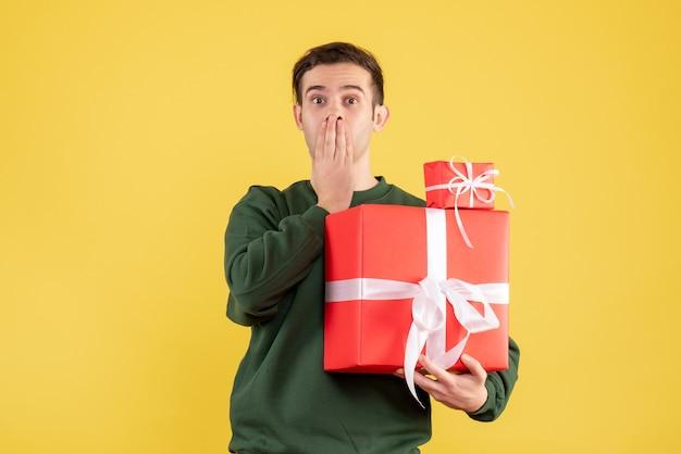 Вид спереди удивился молодой человек с рождественским подарком, стоящий на желтом