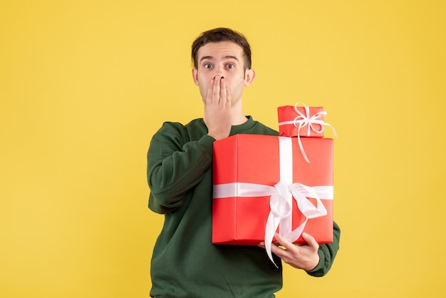 Front view wondered young man with xmas gift standing on yellow