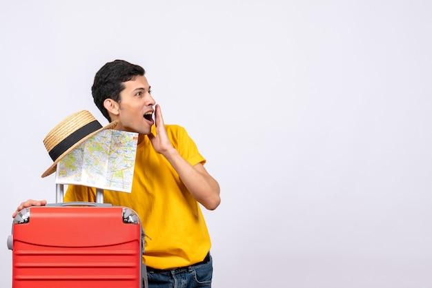 Вид спереди удивился молодой человек в желтой футболке, держащий соломенную шляпу и карту