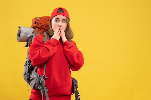 正面図は口に手をつないでバックパックと赤い帽子を持つ若い観光客を不思議に思った