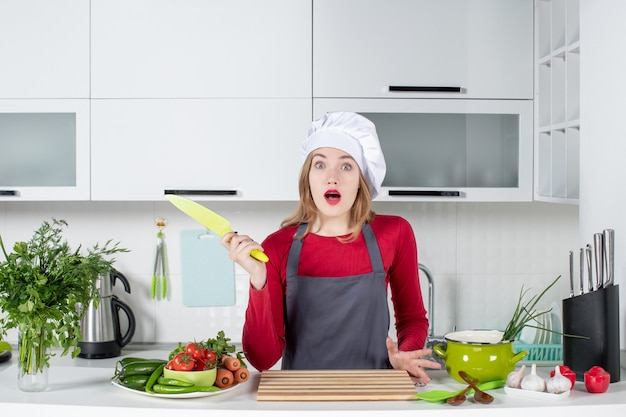 Front view wondered young woman in apron holding up knife