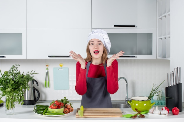 Front view wondered young woman in apron opening her hands