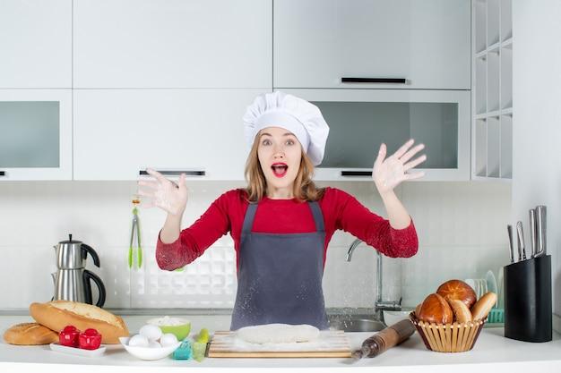 正面図は、キッチンで小麦粉で手を上げるクックハットとエプロンの若い女性を不思議に思った