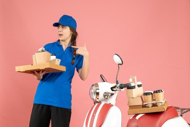 Vista frontale della signora del corriere che si chiedeva in piedi accanto alla motocicletta con in mano caffè e piccole torte su sfondo color pesca pastello pastel