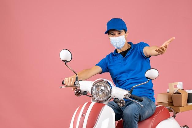 Vista frontale del corriere chiedendosi in maschera medica che indossa un cappello seduto su uno scooter che consegna ordini su sfondo color pesca pastello