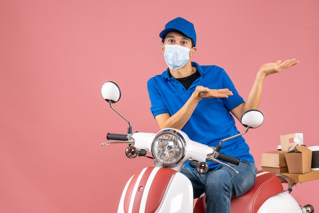 Vista frontale del corriere chiedendosi in maschera medica che indossa un cappello seduto su uno scooter su sfondo color pesca pastello