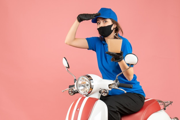 Vista frontale del fattorino che si chiedeva che indossava maschera medica e guanti seduto su uno scooter che consegnava ordini su sfondo color pesca pastello