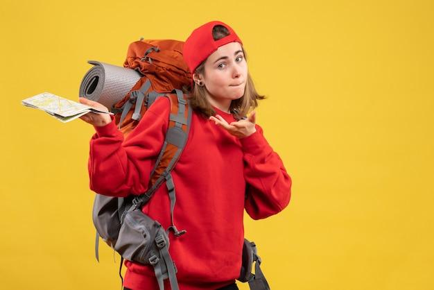 旅行マップを保持している女性のバックパッカーを不思議に思って正面図