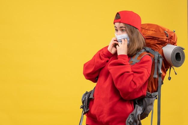 Вид спереди удивленная женщина-турист с рюкзаком и маской на желтой стене