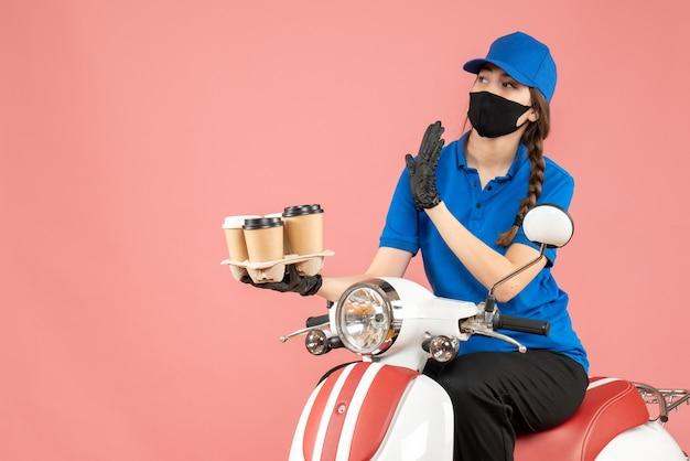 Vista frontale della persona che si chiede consegna femminile che indossa maschera medica e guanti seduto su uno scooter che tiene ordini su sfondo color pesca pastello