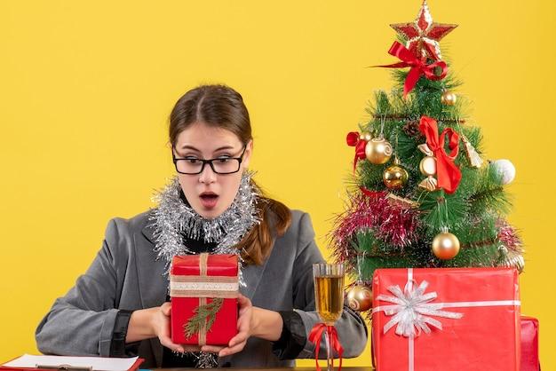 Vista frontale chiedendo ragazza con gli occhiali seduto al tavolo guardando il suo regalo albero di natale e regali cocktail