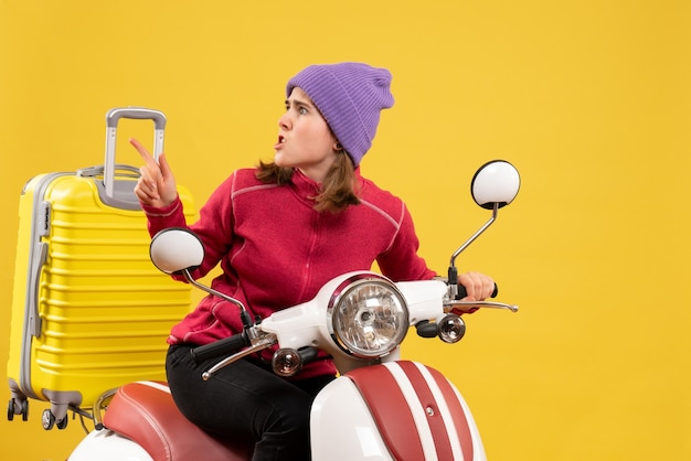 Front view wondering young girl on moped pointing finger left