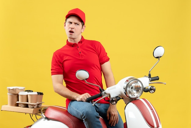 Front view of wondering young guy wearing red blouse and hat delivering orders on yellow background