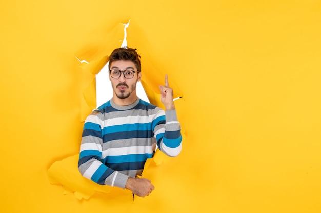 Вид спереди удивленного молодого человека, указывающего пальцем вверх, глядя сквозь рваную бумажную желтую стену