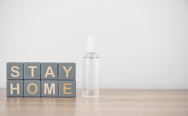 Front view of wooden cubes with stay home and hand sanitizer